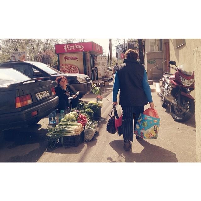 Trotuar de Bucuresti, ingustat de masini si motociclete parcate alaturi de tonete de ziare. Dintre masini apare o vanzatoare de zarzavaturi. Romania moderna? #romaniadoizero #romaniamagica #arielublog